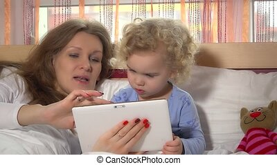 Curious toddler girl with her mom playing with tablet computer in bed
