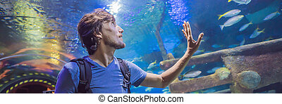 curious tourist watching with interest on shark in oceanarium tunnel BANNER, LONG FORMAT