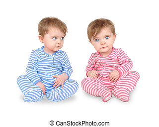 Two identical twins are sitting on a white isolated background. One boy is wearing blue and the other girl is wearing pink. Use it for a personality or family concept.