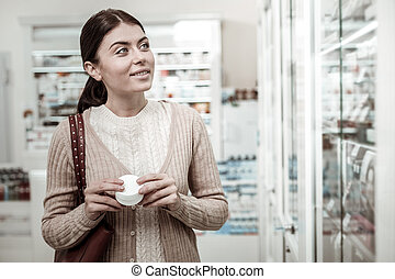 Green-eyed stylish woman feeling curious while choosing cream for sensitive skin