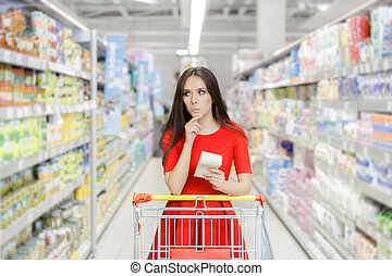Young girl in a market store with a shopping list thinking what to buy