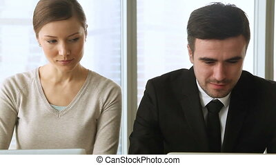 Curious woman spying male colleague, looking at his laptop screen