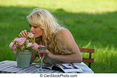young attractive blond taking delight in roses in the green park beside a folding table with wine, roses and a fashion magazine on it