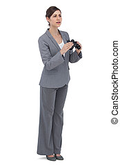 Curious young businesswoman with binoculars