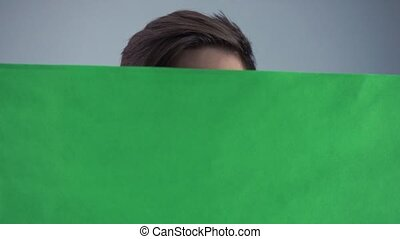 Curious Young man in black shirt holding green key sheet poster gray background