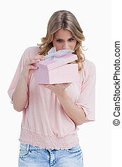 Curious young woman holding a gift while opening it