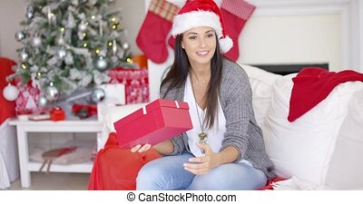 Curious young woman shaking a Christmas gift trying to guess...