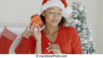 Curious young woman shaking her Christmas gift - Curious...