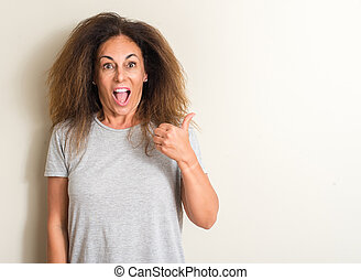 Curled hair brazilian woman pointing with hand and finger up with happy face smiling