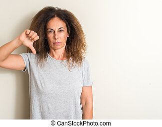 Curled hair brazilian woman with angry face, negative sign showing dislike with thumbs down, rejection concept