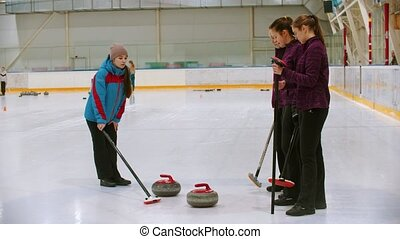 Curling training - the judge measuring the distance between two stones on the ice. Mid shot