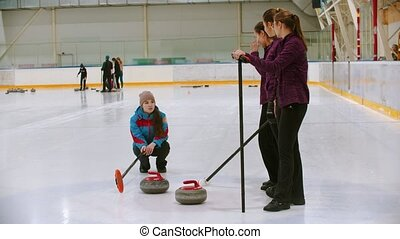 Curling training - the judge measuring the distance between two stones on the ice rink. Mid shot