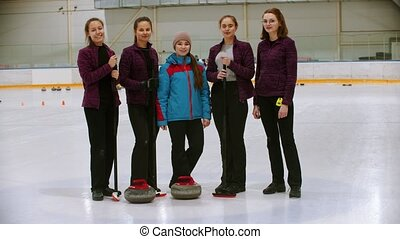 Curling training - the judge standing on the ice rink with her students. Mid shot
