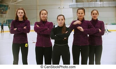 Curling training - the judge standing on the ice rink with her women students - crossing their hands on the chest. Mid shot