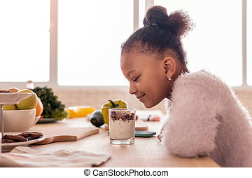 Curly African-American girl looking at sweet pudding with nuts