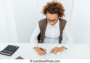 Curly african young woman accountant sitting and writing in office