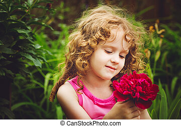 Curly baby with flowers in her hand