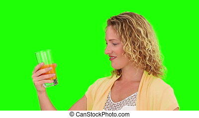 Curly blond female drinking a glass of orange juice