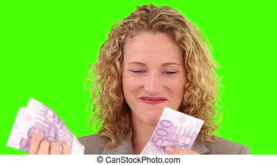 Chroma-key footage of a curly blond haired woman counting her cash