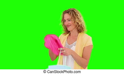 Curly blond haired woman holding a shopping bag