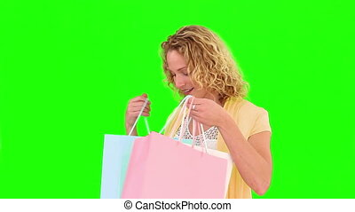 Curly blond haired woman holind shopping bags - Chromakey...