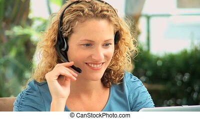 Curly blonde haired woman speaking over the headset in an...