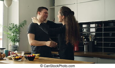 Curly caucasian businesswoman standing behind her husband in the kitchen making him guessing, he opens eyes, they are laughing and smiling discussing his cooking