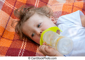 curly child is lying on the coverlet and sucks a bottle of water