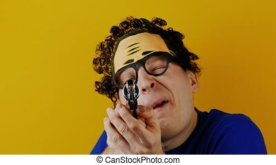curly comical man with toy pistol handgun aims at the camera...