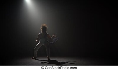 Curly female practicing capoeira in darkness against...