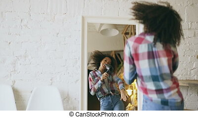 Curly funny african american girl dancing and singing with hair dryer in front of mirror at home