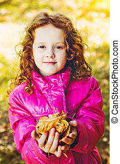 Curly girl in a red jacket with yellow autumn leaves in the hands.