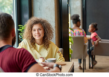Curly girl sitting in cafe with her boyfriend, drinking coffee, eating cakes.