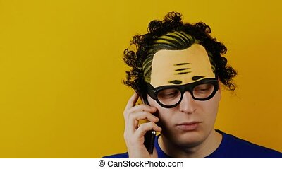 curly guy seriously talking on the smartphone, on yellow...