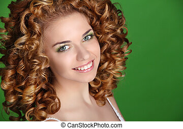 Curly Hair. Attractive smiling woman portrait on green background. Beauty Portrait.