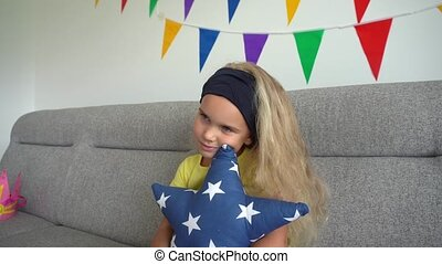 Blond curly hair girl hug star shape pillow and watch tv sitting on sofa. Pretty female child spent leisure at home. Gimbal motion shot