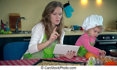 helper girl help her mother with baking cookies. Woman with tablet computer.