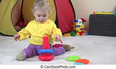 curly haired baby girl playing with colorful child pyramid.