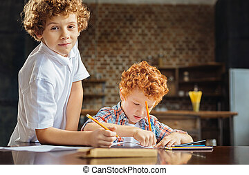 Curly haired brothers drawing together