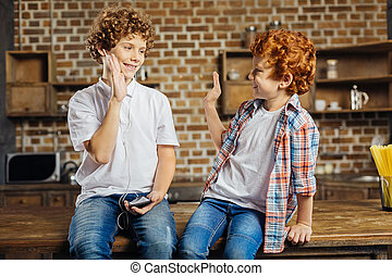 Curly haired brothers high fiving at home