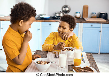 Curly-haired little boys chatting while eating cereals