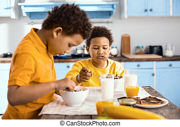 Curly-haired pre-teen boys eating cereals and talking