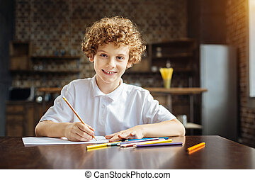 Curly haired preteen boy looking into camera while drawing