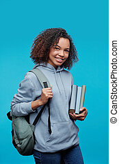 Curly-haired student girl against blue background