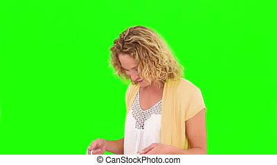 Curly-haired woman buying clothes against a green screen