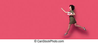 curly haired woman is running after somebody holding a present and gesturing with hands the wait sign on red wall with free space