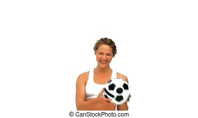 Curly haired woman playing with a soccer ball isolated on a...