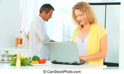 Curly-haired woman showing somthing on her laptop to her...