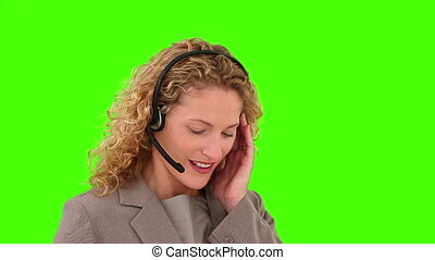 Curly-haired woman speaking over the headset