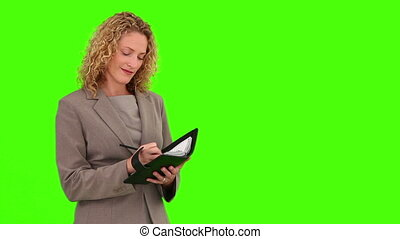 Curly-haired woman writing something on her diary